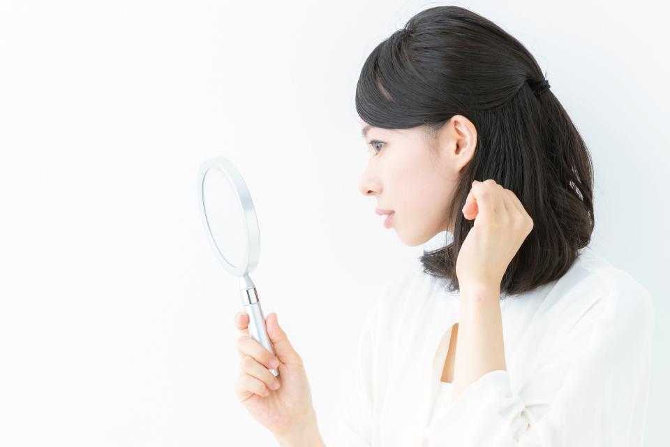 鏡で白髪を探す女性